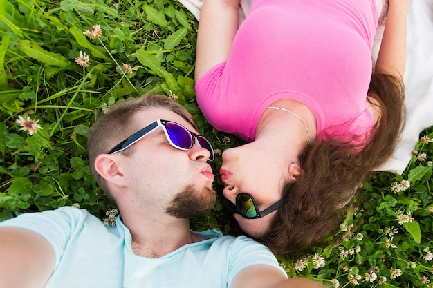 Close up selfie of a young and attractive couple laying down