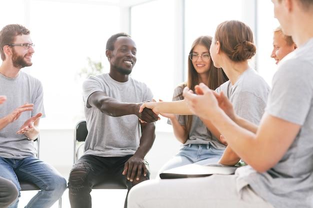 閉じる。会議室に座って握手するセミナー参加者