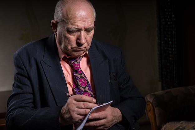 Закройте вверх по старшему лысому бизнесмену в деловом костюме, снимая заметки с серьезным выражением лица.