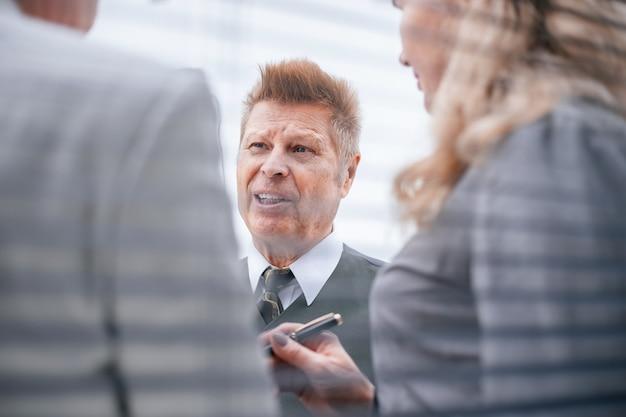 閉じる。従業員と何かを話し合うシニアビジネスマン。ビジネスコンセプト