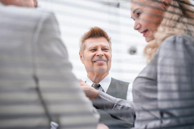 閉じる。彼の同僚と話しているシニアビジネスマン。ビジネスコンセプト