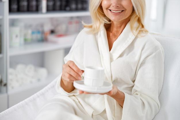 美容院でお茶を持って、白いバスローブで笑っているシニア白人女性を閉じます。