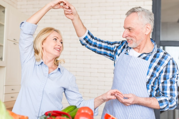 Close-up of senior couple enjoying dancing in the kitchen
