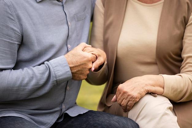 手をつないで年配のカップルを閉じる