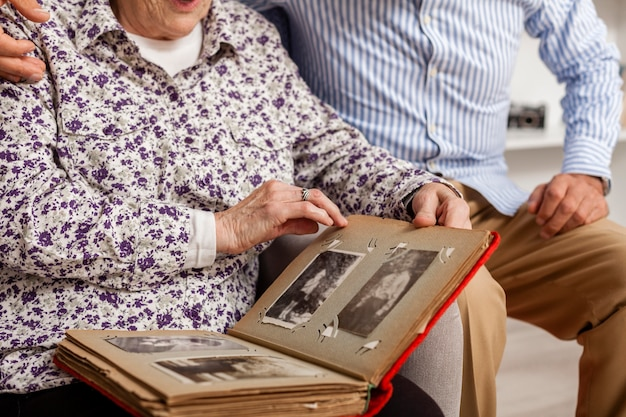 Close-up senior couple holding photo album