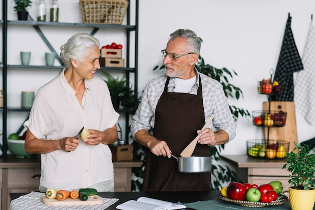 Close-up of senior couple preparing food in the kitchen looking at each other