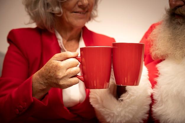 Close-up senior couple toasting with mugs