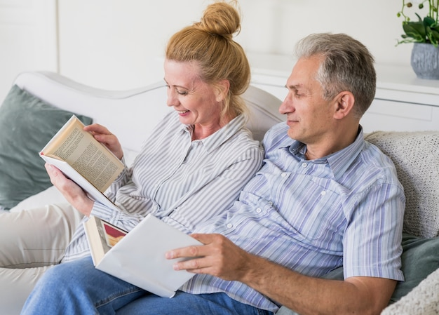 Close-up senior couple with book on a couch