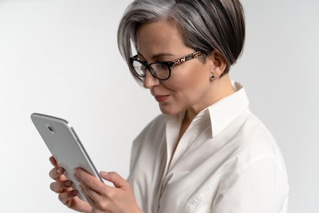Закройте вверх. старшая седая женщина в белой рубашке с помощью цифрового планшета. использование технологий