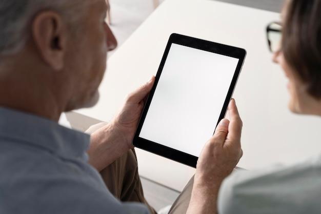 Primo piano uomo anziano che tiene tablet