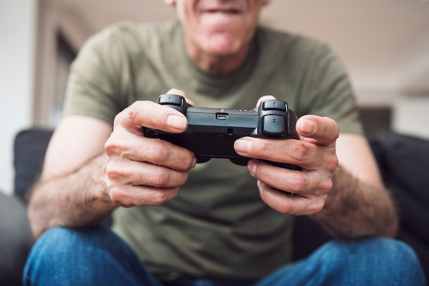 Close-up of senior man holding video game console