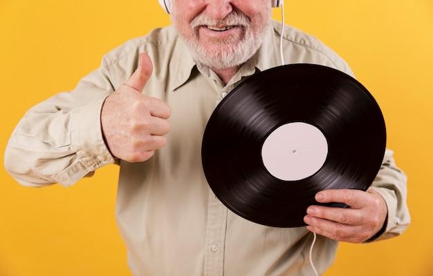 Close-up senior man likes music records