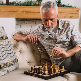 Close-up of senior man playing chess