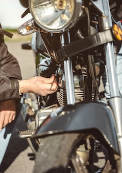 Close up of senior man repairing damaged motorcycle engine on the road