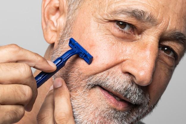 Close-up senior man shaving