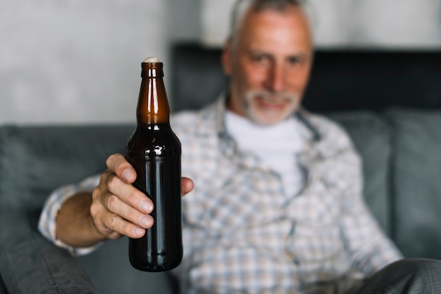 Close-up of a senior man showing beer bottle with froth