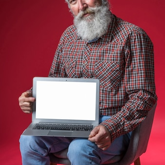 Close-up of senior man showing digital tablet with blank white screen display against red backdrop