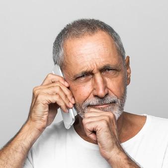Крупным планом старший мужчина разговаривает по телефону