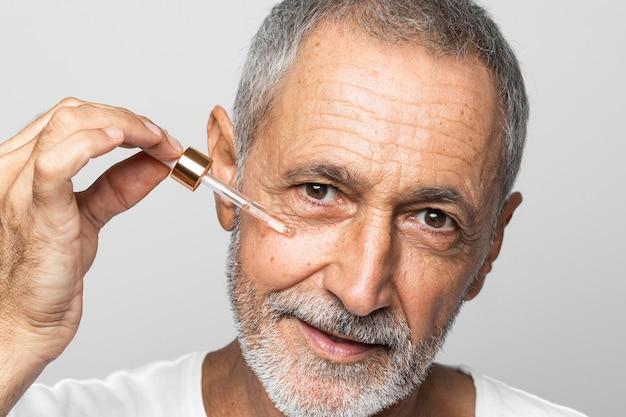 Close-up senior man using serum