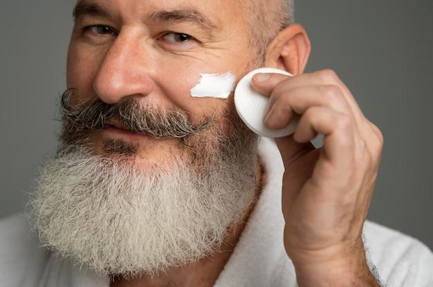 Primo piano uomo anziano con crema per il viso