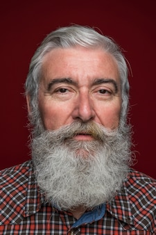 Close-up of senior man with grey beard on colored backdrop