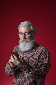 Close-up of a senior man with grey beard using the mobile phone standing against red background