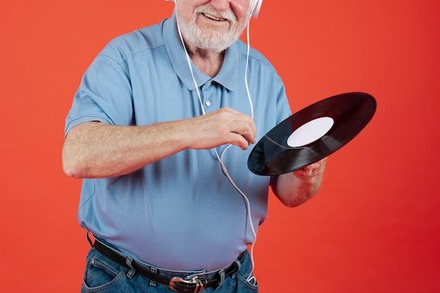 Close-up senior man with music record