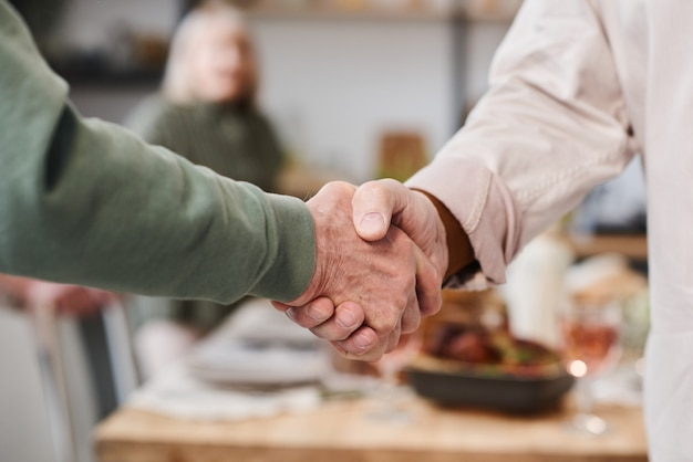 Close-up of senior people shaking hands and greeting each other at a meeting