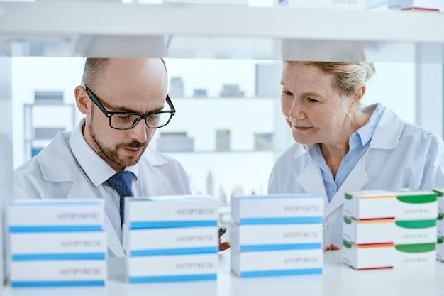 Крупный план. старший фармацевт и его помощник проверяют наличие важных предметов медицинского назначения.
