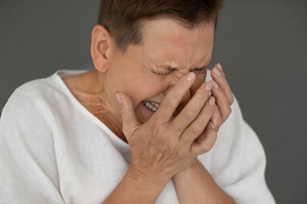 泣いている年配の女性をクローズアップ