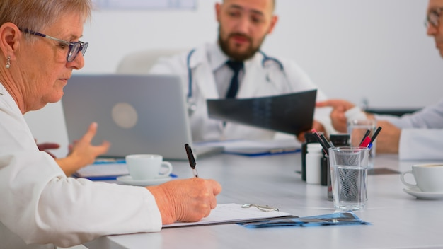 Close up of senior woman doctor taking notes on clipboard while radiologist coworkers discussing in background analysing x-ray and writing on laptop. profesional teamworker having medical meeting