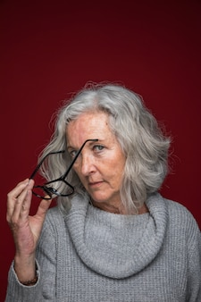 Close-up of a senior woman holding eyeglasses in hand against red backdrop