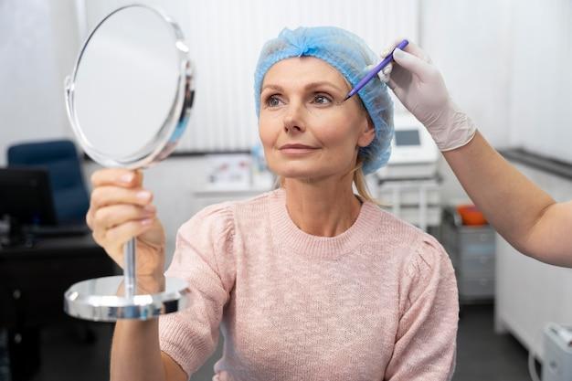 Close up senior woman holding mirror