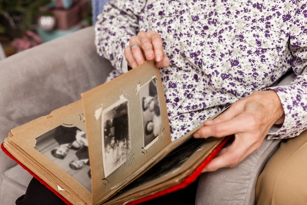 Close-up senior woman looking into photo album