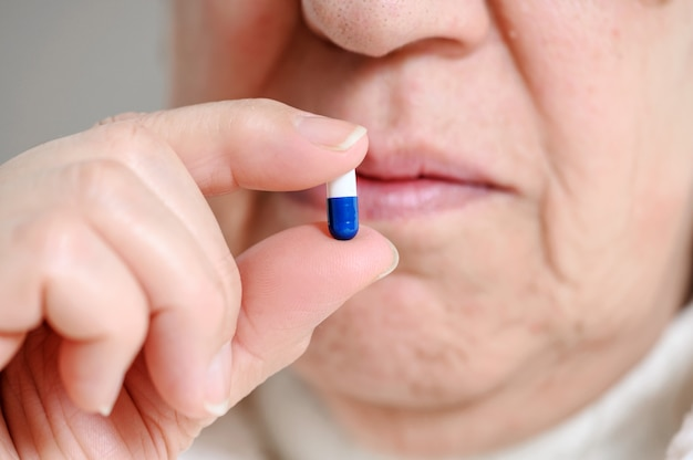 Close up of a senior woman swallowing pill.