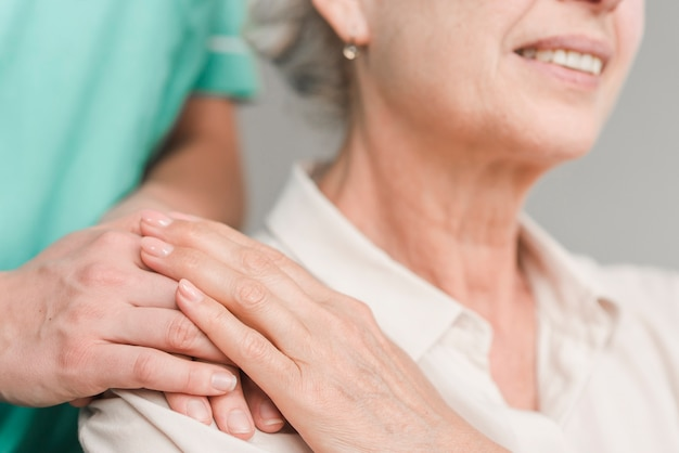 Close-up of senior woman touching nurse hand