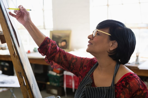 Close up of senior woman wearing apron while painting on paper