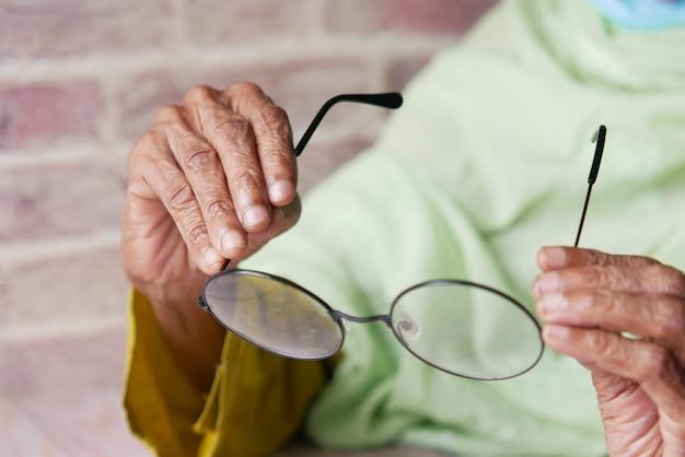 Close up of senior women hand holding old eyeglass