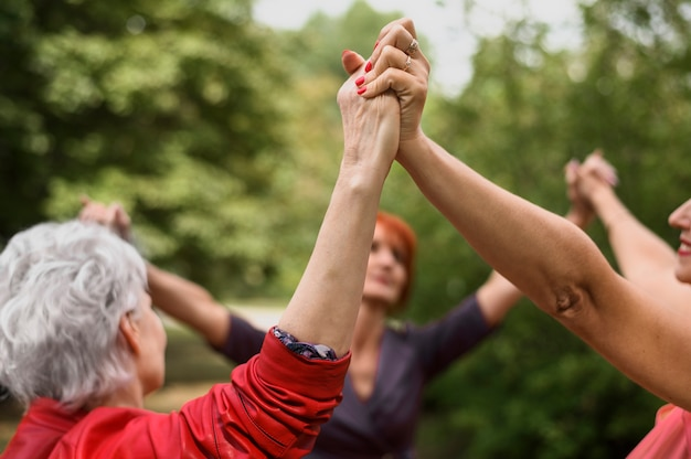 Close-up senior women holding hands