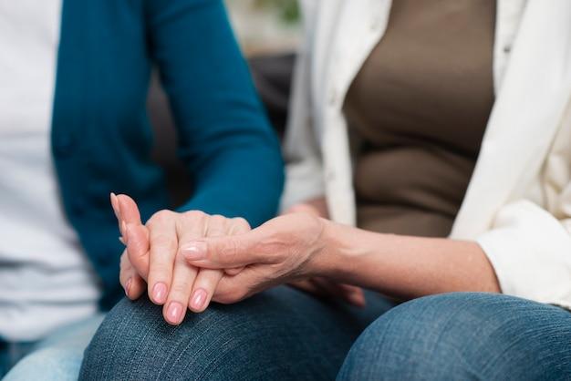 Close-up senior women holding hands