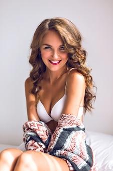 軽い巻き毛を持つ美しい若い女性の官能的な肖像画を閉じ、彼女の朝を楽しみ、リラックスして目を閉じ、シンプルな白いブラと居心地の良いセーターを着ています。