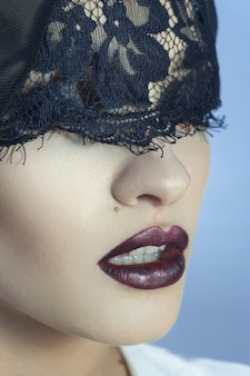 Close up of sensual young lady with purple beautiful lips and lace on eyes in studio