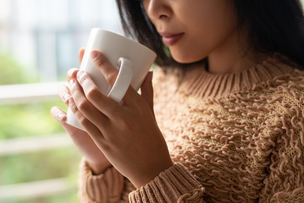 Close-up of serious asian woman in sweater drinking hot coffee