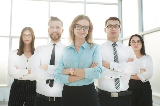 Закройте вверх. серьезная бизнес-леди и ее бизнес-команда, стоящая вместе