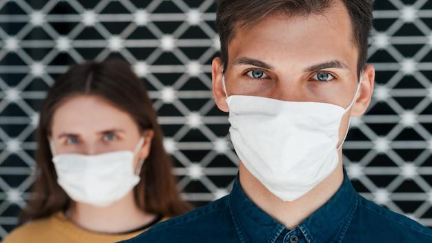 확대. 심각한 남자와 여자 보호 마스크입니다. 건강 보호의 개념