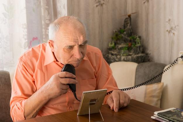 집 안의 나무 탁자에 있는 거울 앞에서 수염을 면도하는 진지한 노인을 닫습니다.