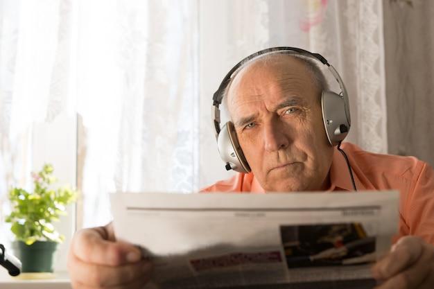 カメラを見つめながら新聞を保持しているヘッドセットで深刻な老人を閉じます。