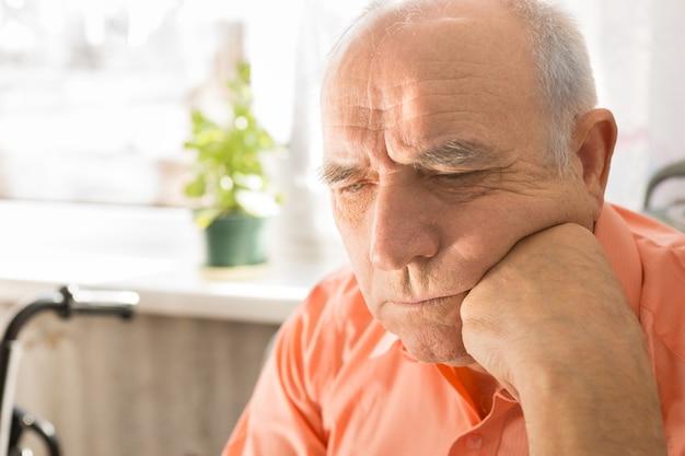 Крупным планом серьезный старший лысый мужчина в оранжевой рубашке, глядя вниз с кулаком на лице
