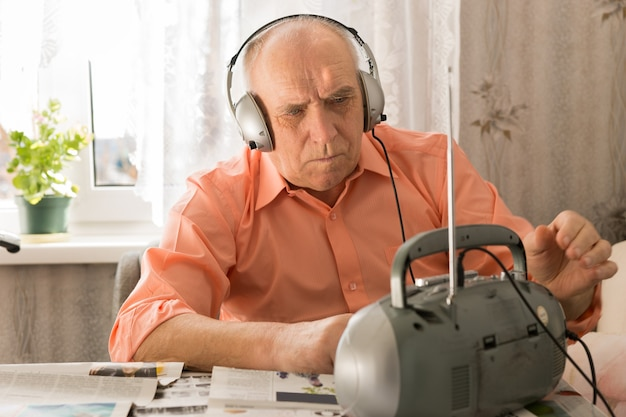 カセットプレーヤーでニュースを聞いている真面目な年配の男性をクローズアップ新聞でリビングルームに真剣に白い座っている。