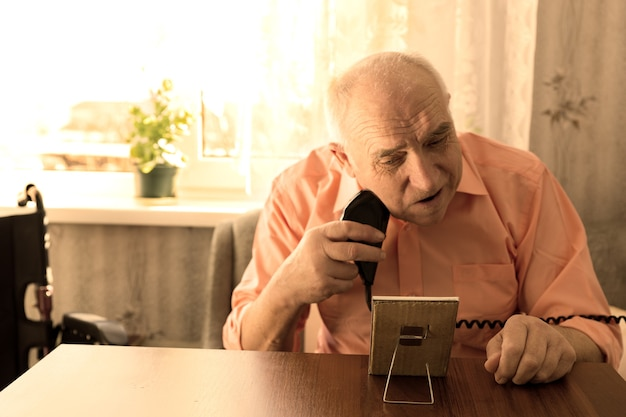 거실에 작은 거울이 있는 나무 테이블에서 전기 면도기로 수염을 면도하는 심각한 노인